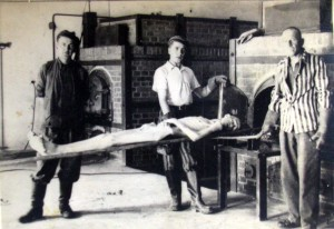 Dachau prisoners placing a corpse in a cremation over folloing the liberation of the camp.